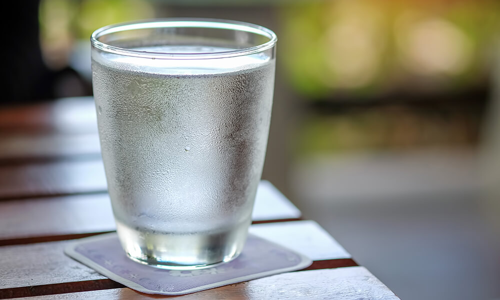 glass of cold water sitting on wooden table in front of window